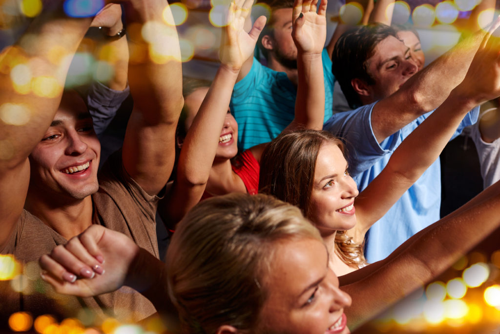 party, holidays, celebration, nightlife and people concept - group of smiling friends waving hands at concert in club